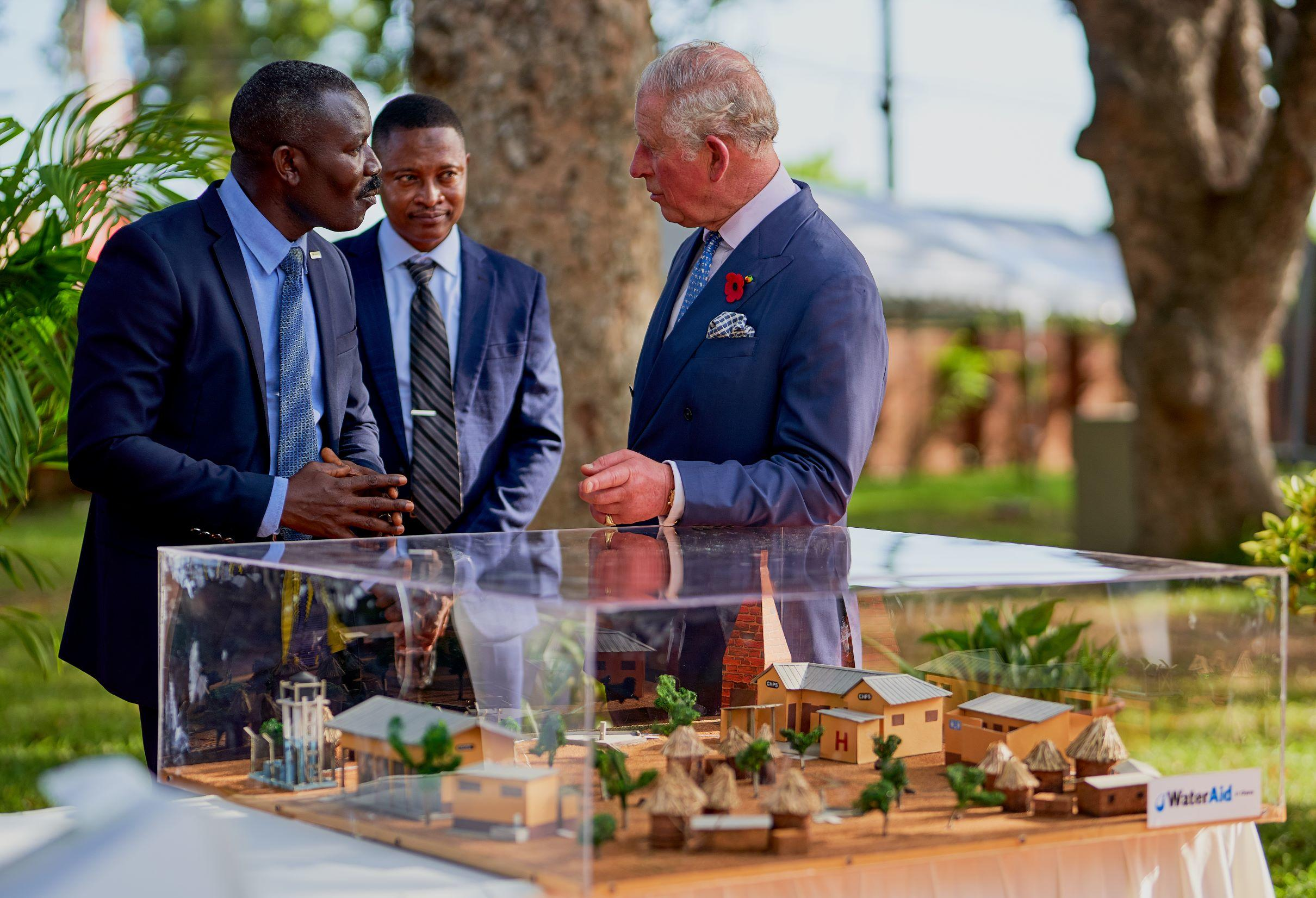 HRH The Prince of Wales listens as Sampson Tettey (far left) and Abdul-Nashiru Mohammed (centre) of WaterAid Ghana explain a model of water and sanitation work in a village, in Accra, Ghana, 5 Nov.